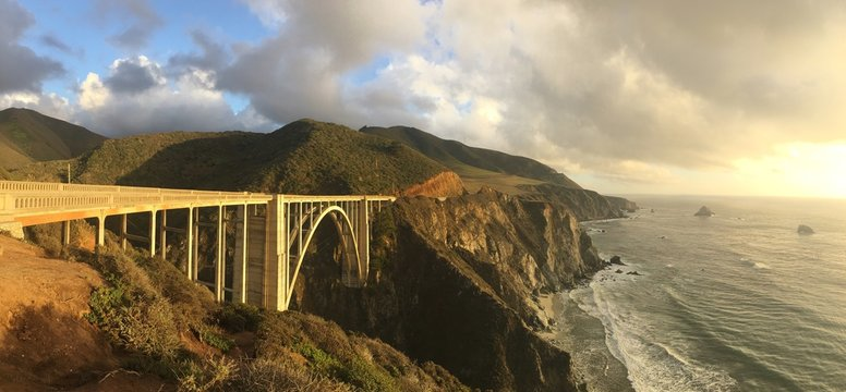 Bixby Creek Bridge And Sea Against Cloudy Sky