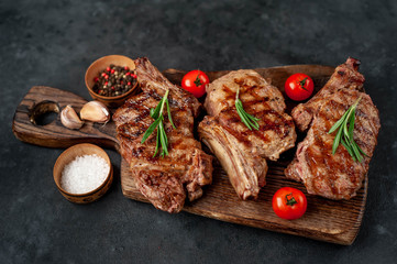 Canvas Prints Meat three grilled beef steaks with spices on a cutting board on a stone background