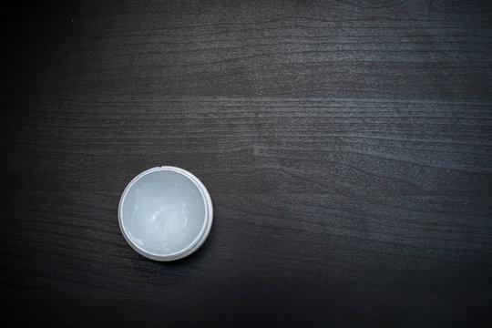 jar of petroleum jelly on dark wooden table