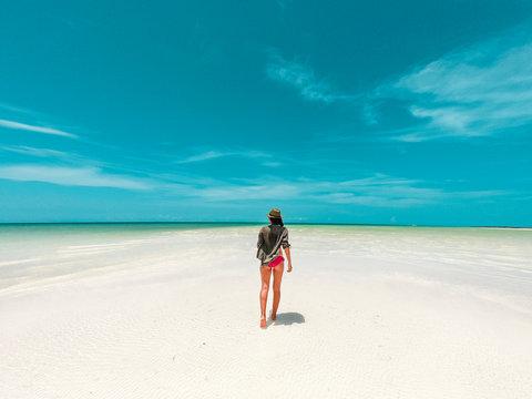 Mujer caminando en bancos de arena Isla Holbox