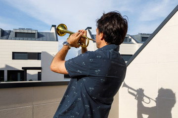 Man playing trumpet on thr terrace in summer. Side view. Covid - 19 Wall mural