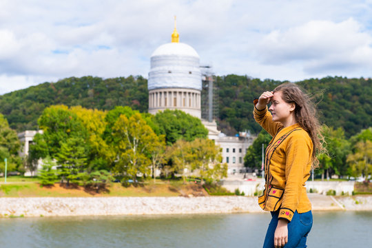 Charleston, West Virginia capital city with woman looking at scaffold construction on state capitol dome from university grounds by river