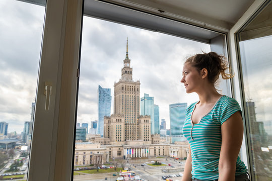 Side view of young woman standing by window windowsill with aerial high angle view of Warsaw, Poland cityscape downtown with palace of culture and science skycrapers