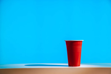 A disposable red plastic party beer cup on a white table or shelf with a bright modern blue background.