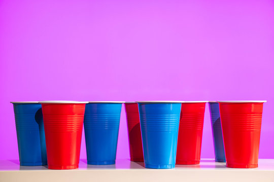 Disposable red and blue plastic party beer cups on a white table or shelf with a bright modern purple background.