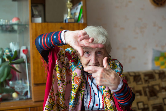 An old woman in bright clothes shows by hands gesture photo frame.