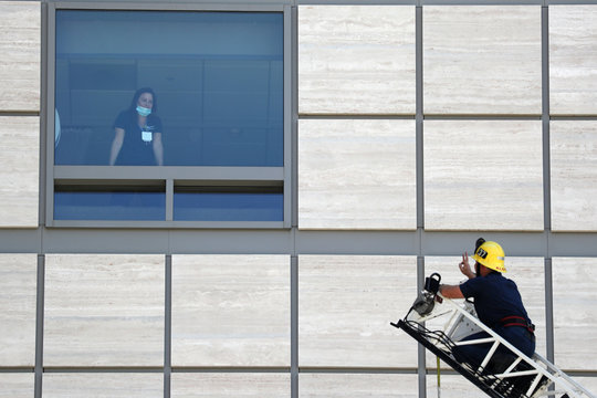 A firefighter gives a sign of appreciation to a healthcare worker during a parade of thanks at UCLA hospital, as the global outbreak of coronavirus disease (COVID-19) continues, in Los Angeles