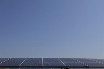 파란 하늘과 태양광 발전 패널이 보이는 풍경 Fotobehang