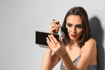 Wall Mural - Beautiful young woman applying makeup against light background