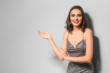 Wall Mural - Young woman with beautiful makeup on light background