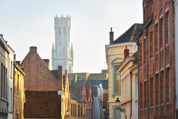Low angle view of a medieval bell tower (Belfry of Bruges) in a historical city center at sunset. Clear blue sky with cirrus clouds. Travel guide, sightseeing theme. Belgium Fototapete