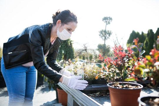 Young woman with face masks outdoors shopping in garden center, Corona virus concept.