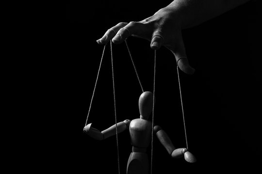 Conceptual image of a hand with strings to control a marionette in monochrome