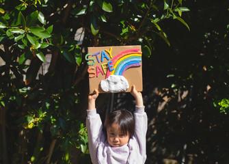 STAY SAFEの文字と虹のボードを掲げる女の子