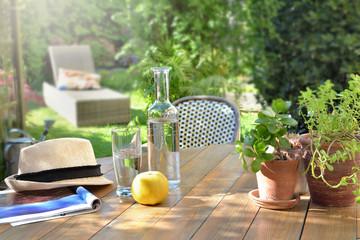 Foto auf Gartenposter Garten close on drink glass and apple on a wooden table in garden background in summer