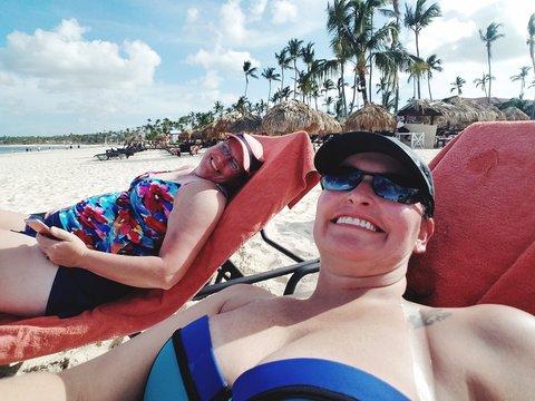 Portrait Of Smiling Women Relaxing On Beach