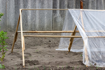 Stage of building a greenhouse from wooden slats and polyethylene in the garden.