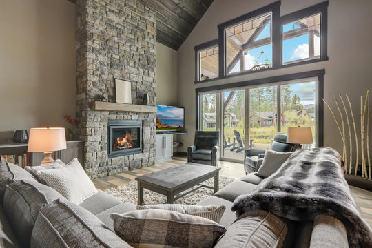 Living room luxury interior with large stone fireplace and leather furniture and huge tall windows with natural tones.
