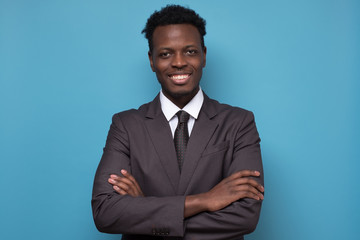 african american businessman wearing a black suit and tie on blue background. Fotobehang