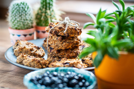 Set of easy to prepare and healthy, homemade oatmeal and blueberry cookies - on beautiful blue plate. Bowl full of blueberries next to it.