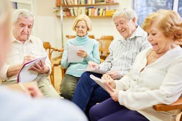 Senioren in einer Gruppentherapie beim Schreiben oder Ausfüllen von Fragebogen