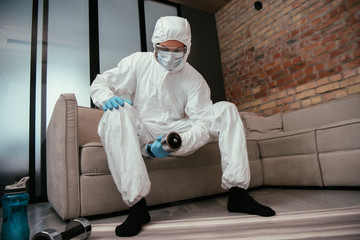 Fototapeta sportive man in hazmat suit, medical mask and goggles exercising with dumbbell in living room