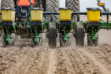 Closeup of tractor and planter in farm field planting corn or soybeans seed in dry, dusty soil during spring season Fototapete