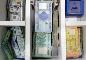 U.S. dollar banknotes and Lebanese pounds are pictured at a currency exchange shop in Beirut