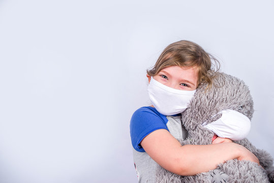Coronavirus protection concept, girl child in a mask with a plush toy bear. COVID-19 Virus protection, social distance, white background copy space