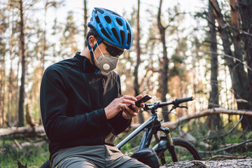 Cyclist wearing pollution mask. Young guy in respirator with filter pm 2.5 with bike in park. Covid 19 Quarantine Sports. Flu epidemic, dust allergy, protection virus. Covid 19 virus concept
