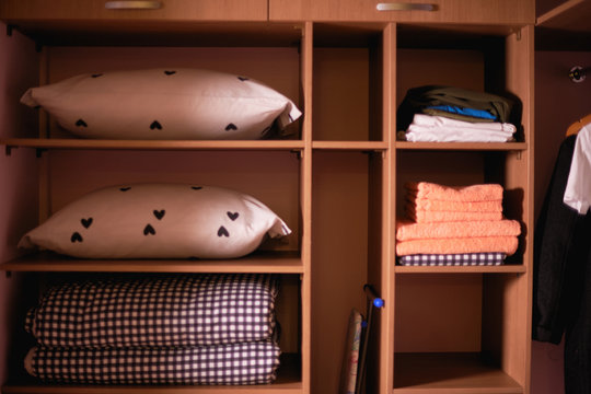 Bed sheets and towels folded in a wardrobe.