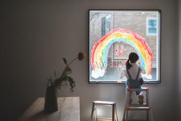 窓にsmile のメッセージと虹の絵を描く少女