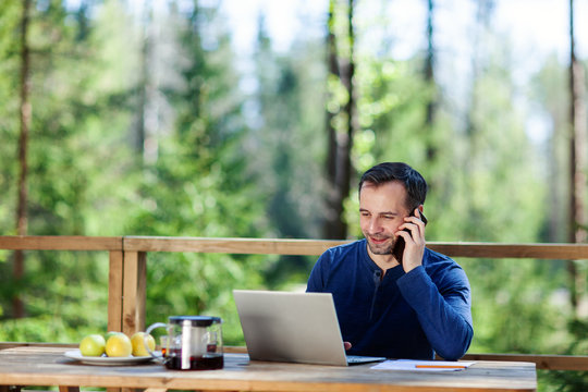 Middle aged businessman talking on cell phone and typing on laptop computer sitting at wooden table on country house terrace. Man working remotely in nature