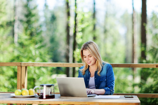 Blonde young woman working on laptop computer sitting at table on wooden balcony of country house