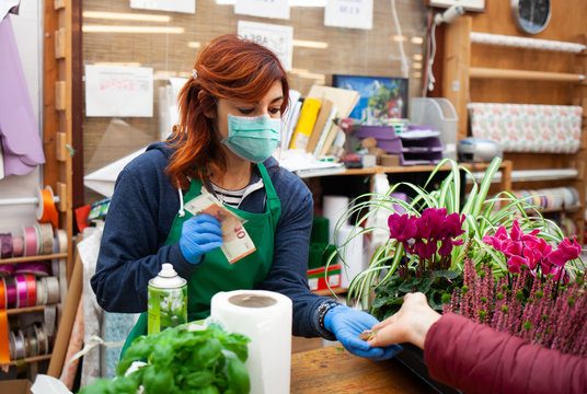 Florist in a nursery receives a payment from a customer wearing a mask and gloves due to the coronavirus covid-19.