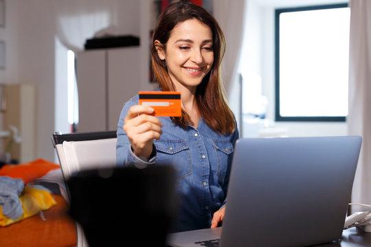 Donna sorridente con i capelli lunghi utilizza la sua carta di credito per fare un ordine attraverso internet con il lap top