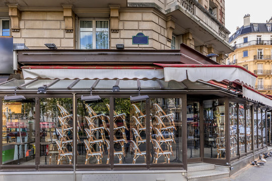 Paris, France - April 17, 2020: Restaurant brasserie on Boulevard Saint Germain is closed due to epidemic of coronavirus COVID19 in Paris. Empty bar, chairs raised, no guests. Sunny spring evening