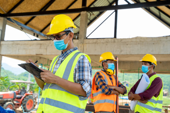 Engineer corporate workers wearing protective masks to prevent dust and covid 19 disease during the inspection in construction site,Coronavirus has turned into a global emergency.