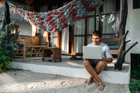 A man uses a laptop while sitting on the terrace of his house. Remote work on the Internet in comfortable conditions.