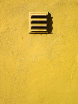 Full Frame Shot Of Yellow Wall With Air Duct