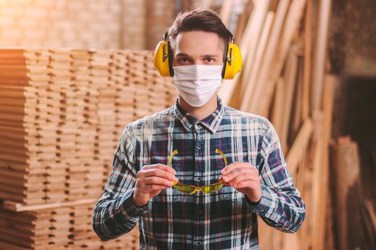 Portrait of professional carpenter wearing medical face mask, hearing protection headphones, protective glasses at sawmill. Male craftsman in protective equipment at wood workshop. Carpentry industry