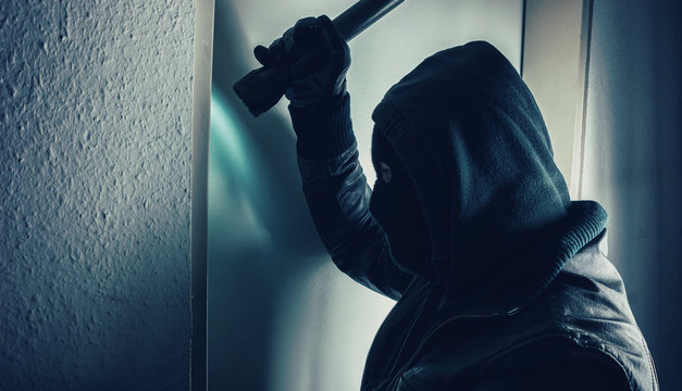Side View Of Burglar With Flashlight At Home