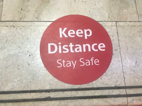 Keep distance stay safe sticker fixed over the marble floor at the bank automatic teller machine queue for the people to follow social distancing to avoid infection of corona virus diseases