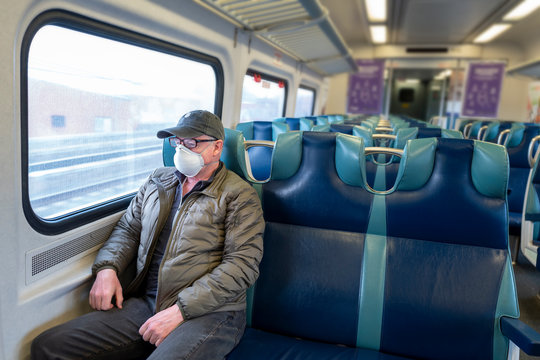 Senior man riding an empty commuter train during the coronavirus pandemic lockdown in NYC.