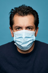 Close up of a man wearing a medical mask.