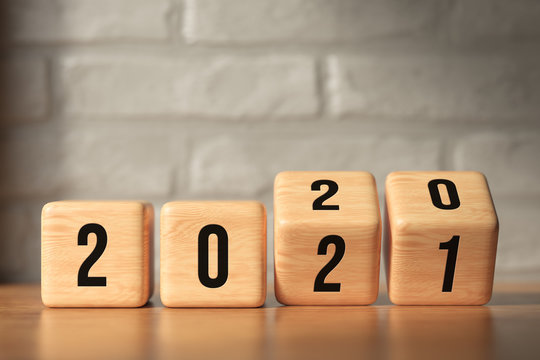 cubes turning from year 2020 to 2021 in front of brick wall background