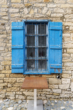 Old window with metal bars and blue open shutters in Limassol. Cyprus