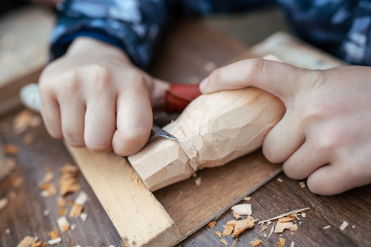 child carves a toy in wood with a knife.  carpenter in the workshop. Close-up of hands