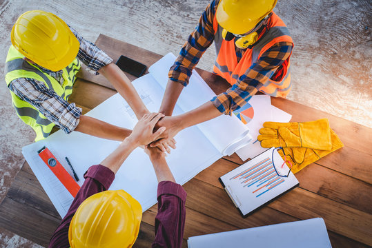 The top view of the team of construction engineers and three architects at the meeting demonstrated symbolic cooperation in drafting the house and building planning in the construction area.