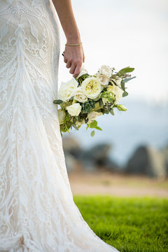 Bride standing outside hold a bouquet of flowers in her hand